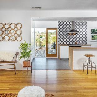 ロサンゼルスの中サイズのコンテンポラリースタイルのおしゃれなキッチン (木材カウンター、エプロンフロントシンク、フラットパネル扉のキャビネット、中間色木目調キャビネット、マルチカラーのキッチンパネル、セラミックタイルのキッチンパネル、黒い調理設備、スレートの床) の写真