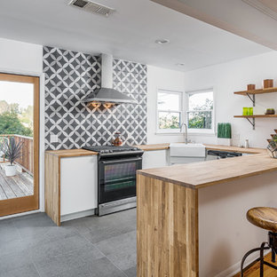 Inspiration for a mid-sized contemporary u-shaped open plan kitchen in Los Angeles with a farmhouse sink, wood benchtops, multi-coloured splashback, black appliances, a peninsula, flat-panel cabinets, medium wood cabinets, ceramic splashback, slate floors and beige benchtop.