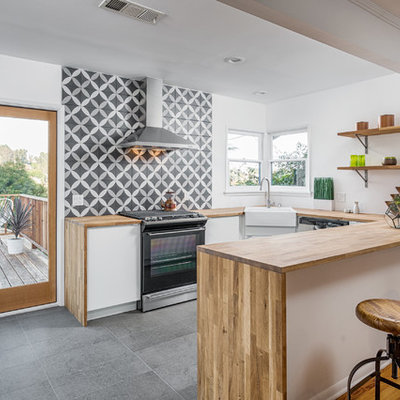 Mid-sized trendy u-shaped slate floor open concept kitchen photo in Los Angeles with a farmhouse sink, wood countertops, multicolored backsplash, black appliances, a peninsula, flat-panel cabinets, medium tone wood cabinets, ceramic backsplash and beige countertops