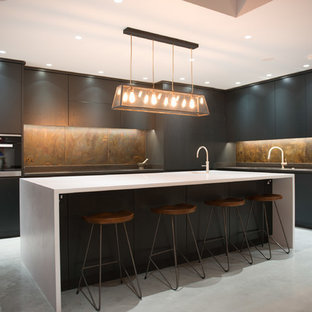 This is an example of an expansive modern l-shaped open plan kitchen in London with a drop-in sink, flat-panel cabinets, dark wood cabinets, quartzite benchtops, multi-coloured splashback, metal splashback, stainless steel appliances, concrete floors, with island, grey floor and white benchtop.