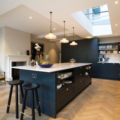Example of a large transitional l-shaped light wood floor kitchen design in London with shaker cabinets, blue cabinets, quartzite countertops, an island and white countertops