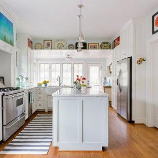 リトルロックのエクレクティックスタイルのおしゃれなキッチン (シェーカースタイル扉のキャビネット、白いキャビネット、白いキッチンパネル、サブウェイタイルのキッチンパネル、無垢フローリング、茶色い床、グレーのキッチンカウンター) の写真