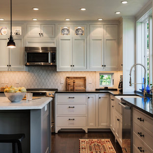 This is an example of a beach style l-shaped eat-in kitchen in Portland Maine with a farmhouse sink, beaded inset cabinets, white cabinets, white splashback, stone tile splashback, stainless steel appliances and granite benchtops.