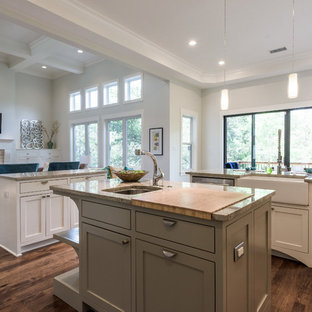 Large transitional u-shaped eat-in kitchen in Austin with a farmhouse sink, shaker cabinets, white cabinets, granite benchtops, slate splashback, stainless steel appliances, dark hardwood floors, multiple islands, brown floor and grey benchtop.