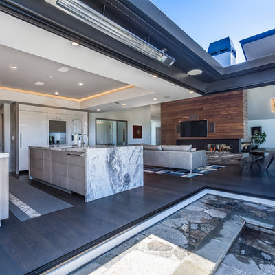 Inspiration for a modern dark wood floor kitchen remodel in San Francisco with a drop-in sink, flat-panel cabinets, medium tone wood cabinets, quartzite countertops, white backsplash, ceramic backsplash, paneled appliances and an island