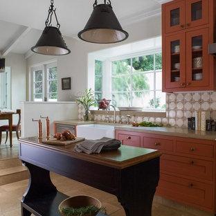 Exempel på ett mellanstort medelhavsstil kök, med en rustik diskho, orange skåp, luckor med infälld panel, bänkskiva i betong, flerfärgad stänkskydd, stänkskydd i terrakottakakel, rostfria vitvaror, kalkstensgolv, en köksö och brunt golv