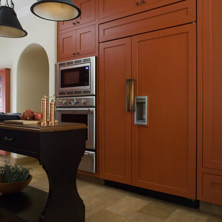 Mid-sized mediterranean eat-in kitchen designs - Mid-sized tuscan galley limestone floor eat-in kitchen photo in San Francisco with orange cabinets, recessed-panel cabinets, concrete countertops, multicolored backsplash, stainless steel appliances and an island