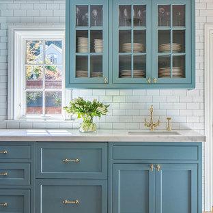 Bild på ett stort funkis l-kök, med luckor med infälld panel, blå skåp, marmorbänkskiva, vitt stänkskydd, stänkskydd i stenkakel, mellanmörkt trägolv, en köksö och en undermonterad diskho