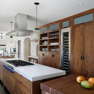 サンフランシスコの中サイズのインダストリアルスタイルのおしゃれなキッチン (フラットパネル扉のキャビネット、中間色木目調キャビネット、シルバーの調理設備の、濃色無垢フローリング、アンダーカウンターシンク、クオーツストーンカウンター、白いキッチンパネル、サブウェイタイルのキッチンパネル、茶色い床) の写真