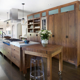 Design ideas for a mid-sized industrial galley open plan kitchen in San Francisco with flat-panel cabinets, medium wood cabinets, stainless steel appliances, dark hardwood floors, with island, an undermount sink, quartz benchtops, white splashback, subway tile splashback and brown floor.