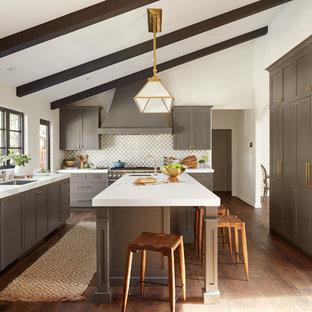 サンフランシスコの地中海スタイルのおしゃれなキッチン (アンダーカウンターシンク、シェーカースタイル扉のキャビネット、グレーのキャビネット、白いキッチンパネル、濃色無垢フローリング、茶色い床、白いキッチンカウンター) の写真