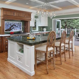 Diseño de cocina comedor lineal, clásica, grande, con armarios con rebordes decorativos, salpicadero gris, salpicadero de azulejos tipo metro, electrodomésticos de acero inoxidable, una isla, suelo de madera clara, puertas de armario de madera oscura y encimeras verdes