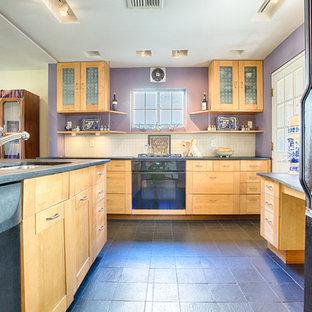 フィラデルフィアの中サイズのエクレクティックスタイルのおしゃれなキッチン (アンダーカウンターシンク、ガラス扉のキャビネット、淡色木目調キャビネット、ソープストーンカウンター、白いキッチンパネル、モザイクタイルのキッチンパネル、黒い調理設備、スレートの床、黒い床) の写真