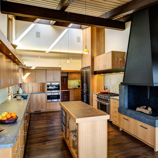 Large midcentury u-shaped eat-in kitchen in San Francisco with an undermount sink, flat-panel cabinets, light wood cabinets, soapstone benchtops, grey splashback, porcelain splashback, stainless steel appliances, dark hardwood floors, with island, brown floor and brown benchtop.