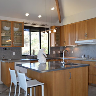 Small contemporary u-shaped open plan kitchen in San Luis Obispo with a single-bowl sink, glass-front cabinets, medium wood cabinets, concrete benchtops, grey splashback, ceramic splashback, white appliances, concrete floors and with island.
