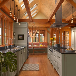 Inspiration for a country galley eat-in kitchen in Burlington with an undermount sink, recessed-panel cabinets, green cabinets, stainless steel appliances, medium hardwood floors, with island and black benchtop.