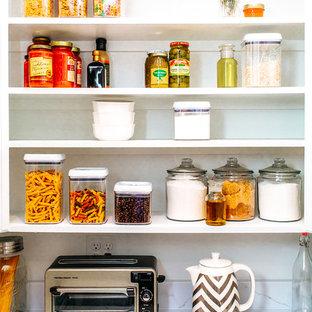 オースティンの大きいカントリー風おしゃれなキッチン (シェーカースタイル扉のキャビネット、白いキャビネット、御影石カウンター、白いキッチンパネル、シルバーの調理設備、竹フローリング、茶色い床、白いキッチンカウンター) の写真