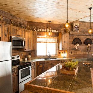 ミネアポリスの中サイズのラスティックスタイルのおしゃれなキッチン (ドロップインシンク、シェーカースタイル扉のキャビネット、中間色木目調キャビネット、ラミネートカウンター、茶色いキッチンパネル、木材のキッチンパネル、シルバーの調理設備の、リノリウムの床、ベージュの床、グレーのキッチンカウンター) の写真