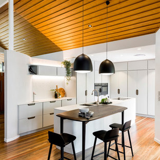 Photo of a mid-sized contemporary l-shaped eat-in kitchen in Brisbane with an undermount sink, flat-panel cabinets, white cabinets, white splashback, black appliances, medium hardwood floors, with island, brown floor and white benchtop.