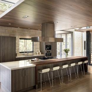 Modelo de cocina minimalista con fregadero bajoencimera, armarios con paneles lisos, puertas de armario de madera en tonos medios, electrodomésticos de acero inoxidable, suelo de madera en tonos medios y una isla
