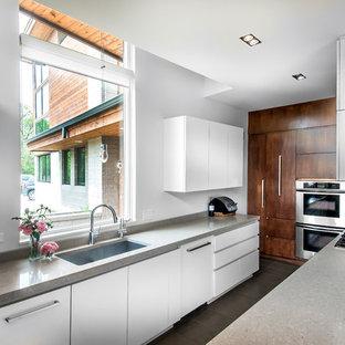 他の地域の中くらいのモダンスタイルのおしゃれなキッチン (アンダーカウンターシンク、フラットパネル扉のキャビネット、白いキャビネット、シルバーの調理設備、御影石カウンター、ライムストーンの床、ベージュの床) の写真