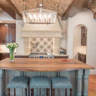 Inspiration för ett stort medelhavsstil kök, med en rustik diskho, luckor med infälld panel, skåp i mörkt trä, flerfärgad stänkskydd, rostfria vitvaror, klinkergolv i terrakotta, en köksö, granitbänkskiva, stänkskydd i mosaik och orange golv