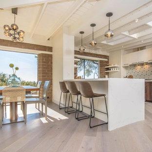 Idee per una cucina minimalista con ante lisce, ante in legno scuro, paraspruzzi bianco, elettrodomestici in acciaio inossidabile, parquet chiaro, penisola, pavimento beige e top bianco