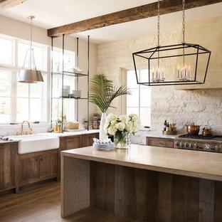 Wohnküche mit Landhausspüle, Schränken im Used-Look, Küchenrückwand in Beige, Kücheninsel, braunem Boden und beiger Arbeitsplatte in Cleveland