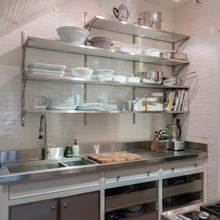 Kleine Küche in L-Form mit Vorratsschrank, Unterbauwaschbecken, offenen Schränken, Edelstahlfronten, Edelstahl-Arbeitsplatte, Küchenrückwand in Weiß, Rückwand aus Keramikfliesen und Küchengeräten aus Edelstahl in Chicago