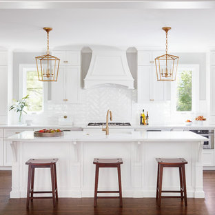 Large transitional l-shaped open plan kitchen in Chicago with shaker cabinets, white cabinets, white splashback, stainless steel appliances, with island, an undermount sink, marble benchtops, porcelain splashback, dark hardwood floors and brown floor.