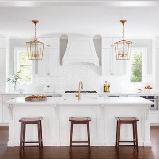 Offene, Große Klassische Küche in L-Form mit Schrankfronten im Shaker-Stil, weißen Schränken, Küchenrückwand in Weiß, Küchengeräten aus Edelstahl, Kücheninsel, Unterbauwaschbecken, Marmor-Arbeitsplatte, Rückwand aus Porzellanfliesen, dunklem Holzboden und braunem Boden in Chicago