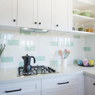 ブリスベンの中サイズのシャビーシック調のおしゃれなキッチン (ダブルシンク、シェーカースタイル扉のキャビネット、白いキャビネット、クオーツストーンカウンター、緑のキッチンパネル、サブウェイタイルのキッチンパネル、白い調理設備、濃色無垢フローリング、アイランドなし、赤い床、白いキッチンカウンター) の写真