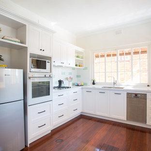 ブリスベンの中くらいのシャビーシック調のおしゃれなキッチン (ダブルシンク、シェーカースタイル扉のキャビネット、白いキャビネット、クオーツストーンカウンター、緑のキッチンパネル、サブウェイタイルのキッチンパネル、白い調理設備、濃色無垢フローリング、アイランドなし、赤い床、白いキッチンカウンター) の写真