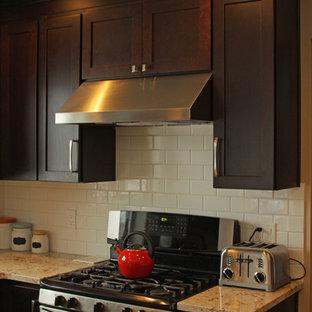 デトロイトの中サイズのエクレクティックスタイルのおしゃれなキッチン (エプロンフロントシンク、シェーカースタイル扉のキャビネット、茶色いキャビネット、クオーツストーンカウンター、白いキッチンパネル、サブウェイタイルのキッチンパネル、シルバーの調理設備の、無垢フローリング、茶色い床) の写真