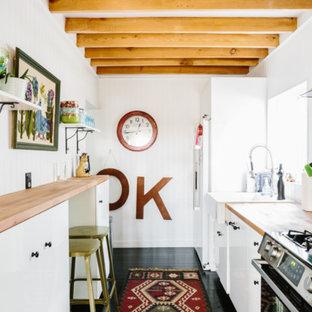 Свежая идея для дизайна: маленькая параллельная кухня в стиле кантри с раковиной в стиле кантри, плоскими фасадами, белыми фасадами, деревянной столешницей, белым фартуком, фартуком из дерева, техникой из нержавеющей стали, полом из бамбука и черным полом без острова - отличное фото интерьера