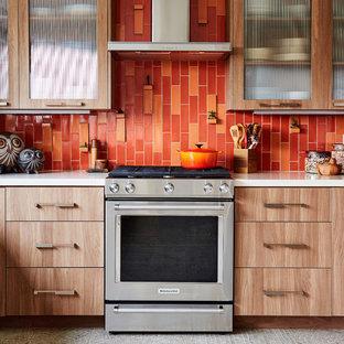 ロサンゼルスの中サイズのコンテンポラリースタイルのおしゃれなキッチン (シングルシンク、ガラス扉のキャビネット、中間色木目調キャビネット、クオーツストーンカウンター、オレンジのキッチンパネル、セラミックタイルのキッチンパネル、シルバーの調理設備、磁器タイルの床、アイランドなし、グレーの床) の写真