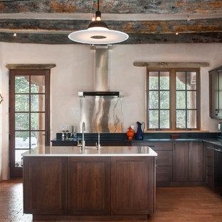 アルバカーキの大きいサンタフェスタイルのおしゃれなキッチン (シングルシンク、シェーカースタイル扉のキャビネット、濃色木目調キャビネット、メタリックのキッチンパネル、無垢フローリング) の写真