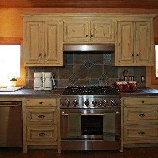 Exempel på ett mycket stort lantligt kök, med en nedsänkt diskho, luckor med upphöjd panel, skåp i slitet trä, kaklad bänkskiva, grått stänkskydd, stänkskydd i stenkakel, rostfria vitvaror, betonggolv och en köksö
