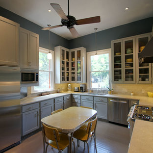 Photo of a mid-sized traditional u-shaped separate kitchen in Austin with a double-bowl sink, glass-front cabinets, grey cabinets, limestone benchtops, beige splashback, subway tile splashback, stainless steel appliances, painted wood floors and no island.
