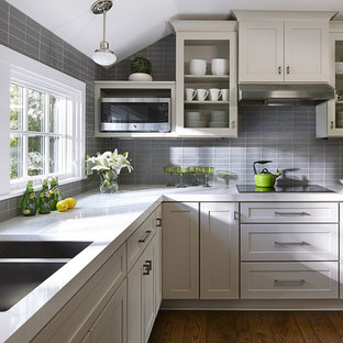 Design ideas for a mid-sized transitional l-shaped kitchen in Minneapolis with grey cabinets, grey splashback, glass tile splashback, stainless steel appliances, no island, a double-bowl sink, dark hardwood floors and glass-front cabinets.