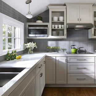 Idee per una cucina a L classica di medie dimensioni con ante grigie, paraspruzzi grigio, paraspruzzi con piastrelle di vetro, elettrodomestici in acciaio inossidabile, nessuna isola, lavello a doppia vasca, parquet scuro e ante di vetro