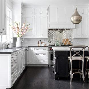 ニューヨークの中サイズのビーチスタイルのおしゃれなキッチン (ドロップインシンク、落し込みパネル扉のキャビネット、白いキャビネット、大理石カウンター、白いキッチンパネル、ミラータイルのキッチンパネル、シルバーの調理設備の、無垢フローリング、茶色い床、マルチカラーのキッチンカウンター) の写真