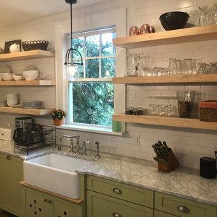 他の地域の中サイズのカントリー風おしゃれなキッチン (エプロンフロントシンク、シェーカースタイル扉のキャビネット、緑のキャビネット、御影石カウンター、白いキッチンパネル、サブウェイタイルのキッチンパネル、シルバーの調理設備、無垢フローリング、茶色い床、グレーのキッチンカウンター) の写真