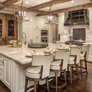 Geräumige Klassische Küche in L-Form mit Landhausspüle, profilierten Schrankfronten, weißen Schränken, Granit-Arbeitsplatte, Küchenrückwand in Weiß, Rückwand aus Backstein, Küchengeräten aus Edelstahl, braunem Holzboden, Kücheninsel, braunem Boden und beiger Arbeitsplatte in Omaha