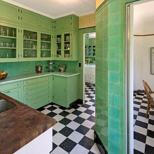 ロサンゼルスの巨大な地中海スタイルのおしゃれなキッチン (ダブルシンク、ガラス扉のキャビネット、緑のキャビネット、タイルカウンター、緑のキッチンパネル、セラミックタイルのキッチンパネル、クッションフロア、アイランドなし) の写真