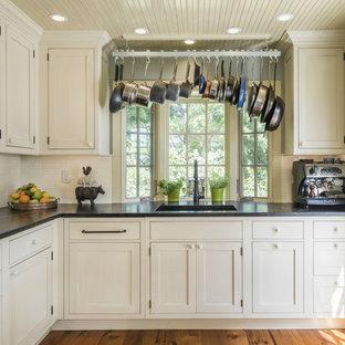 Große Klassische Küche in U-Form mit Kassettenfronten, beigen Schränken, Speckstein-Arbeitsplatte, Küchenrückwand in Beige, Rückwand aus Keramikfliesen, braunem Holzboden, Elektrogeräten mit Frontblende und braunem Boden in Sonstige