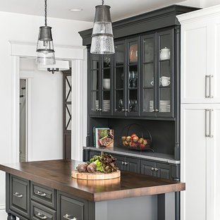 This is an example of a mid-sized traditional u-shaped eat-in kitchen in Chicago with a farmhouse sink, shaker cabinets, white cabinets, quartz benchtops, white splashback, porcelain splashback, stainless steel appliances, dark hardwood floors, a peninsula and brown floor.