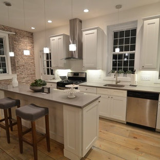 Mid-sized rustic eat-in kitchen ideas - Example of a mid-sized mountain style l-shaped light wood floor and brown floor eat-in kitchen design in Boston with an undermount sink, shaker cabinets, white cabinets, solid surface countertops, white backsplash, subway tile backsplash, stainless steel appliances and an island