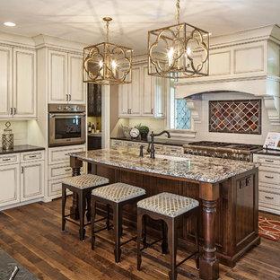 Mittelgroße, Offene Klassische Küche in L-Form mit Unterbauwaschbecken, weißen Schränken, Granit-Arbeitsplatte, Küchenrückwand in Weiß, Küchengeräten aus Edelstahl, dunklem Holzboden, Kücheninsel, Kassettenfronten und Rückwand aus Metrofliesen in Omaha