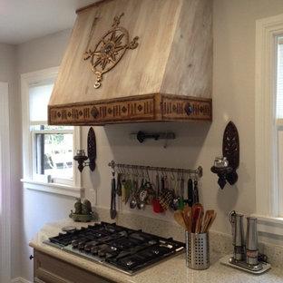Modelo de cocina en L, rural, sin isla, con fregadero sobremueble, armarios con paneles empotrados, puertas de armario grises, encimera de vidrio reciclado, electrodomésticos de acero inoxidable y suelo vinílico